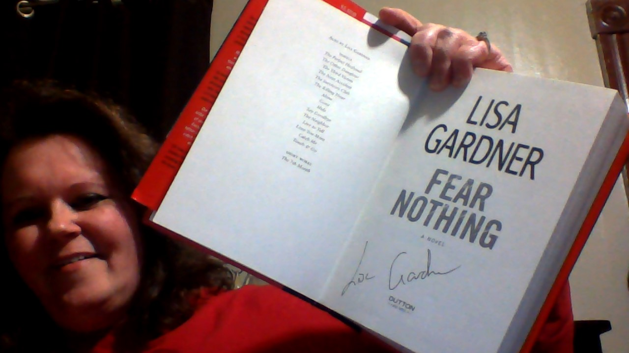 Me holding Lisa Gardner's book open to show others her autograph
